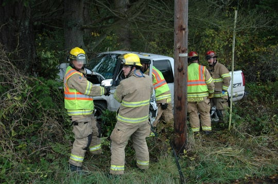 North Kitsap Fire & Rescue crew members work at the scene of a single-vehicle accident on Saturday.