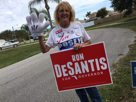 Lois Lacoste, a board member of the North Brevard Republican Club, waves with a Mickey Mouse hand and in the other hand, holds a sign supporting Ron DeSantis.