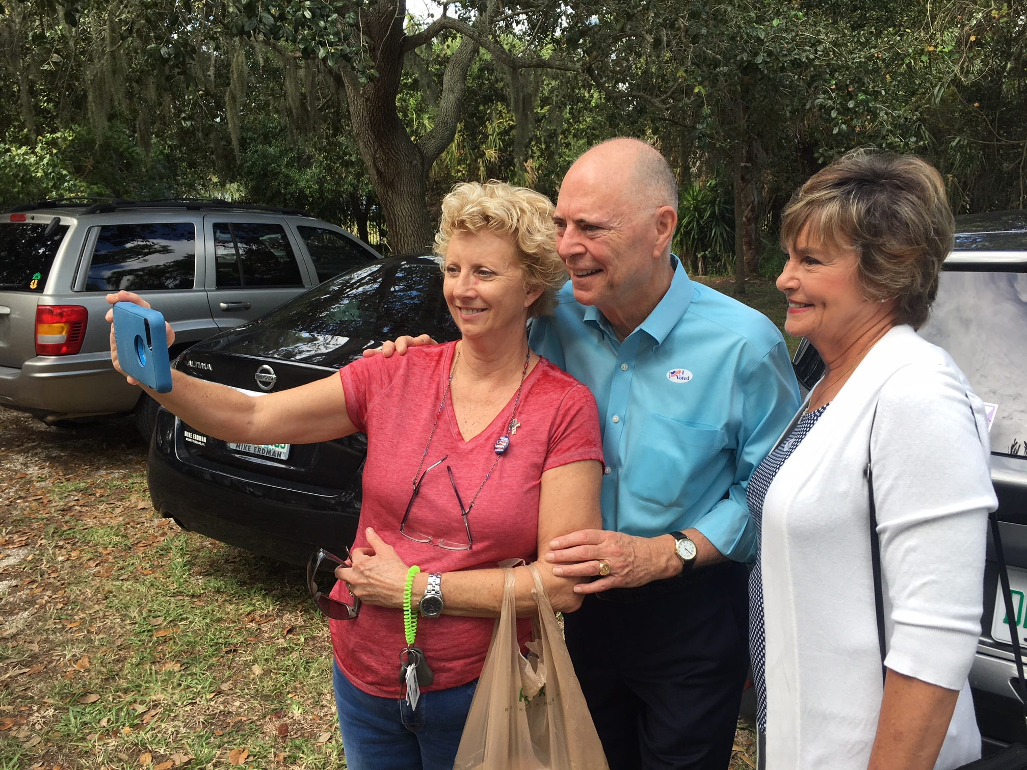 Dottie Jelinek does a selfie with Congressman Bill and Katie Posey after voting at Cocoa Rockledge Garden Club.