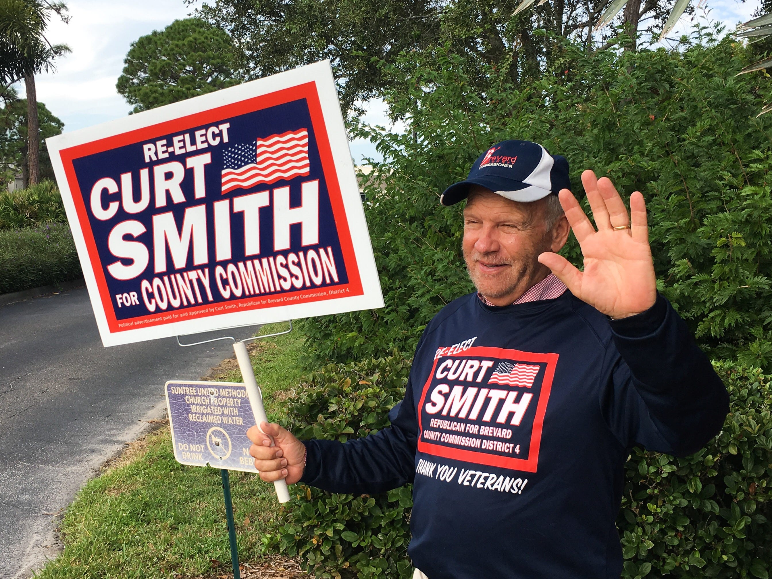 Curt Smith waving to vehicles from the entrance of Suntree United Methodist Church off of N. Wickham Road.