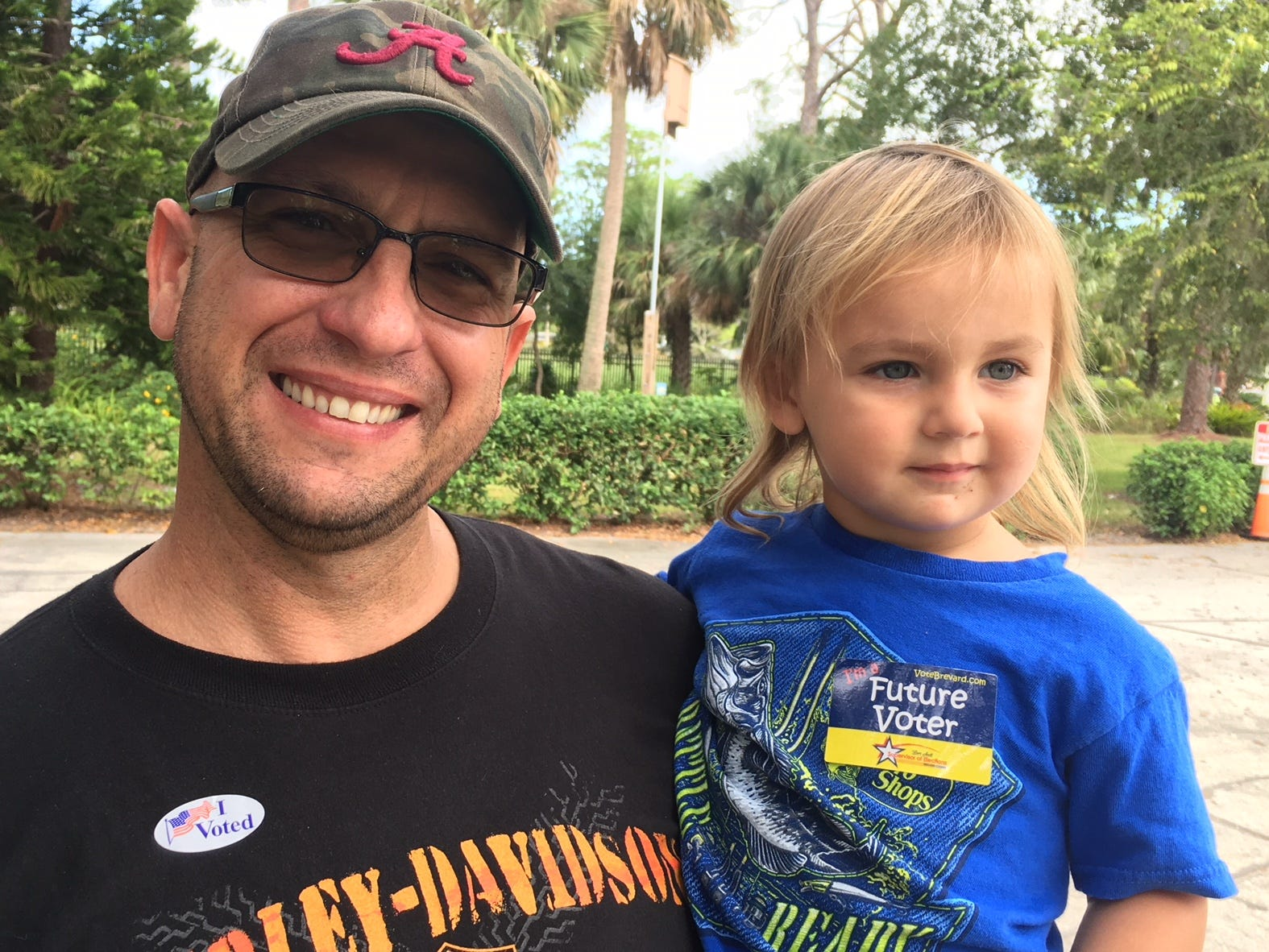 "Elliot Collins with his son Jackson sporting a "" future voter"" sticker after Elliot and his wife Hailey voted at Cocoa Rockledge Garden Club in Rockledge."