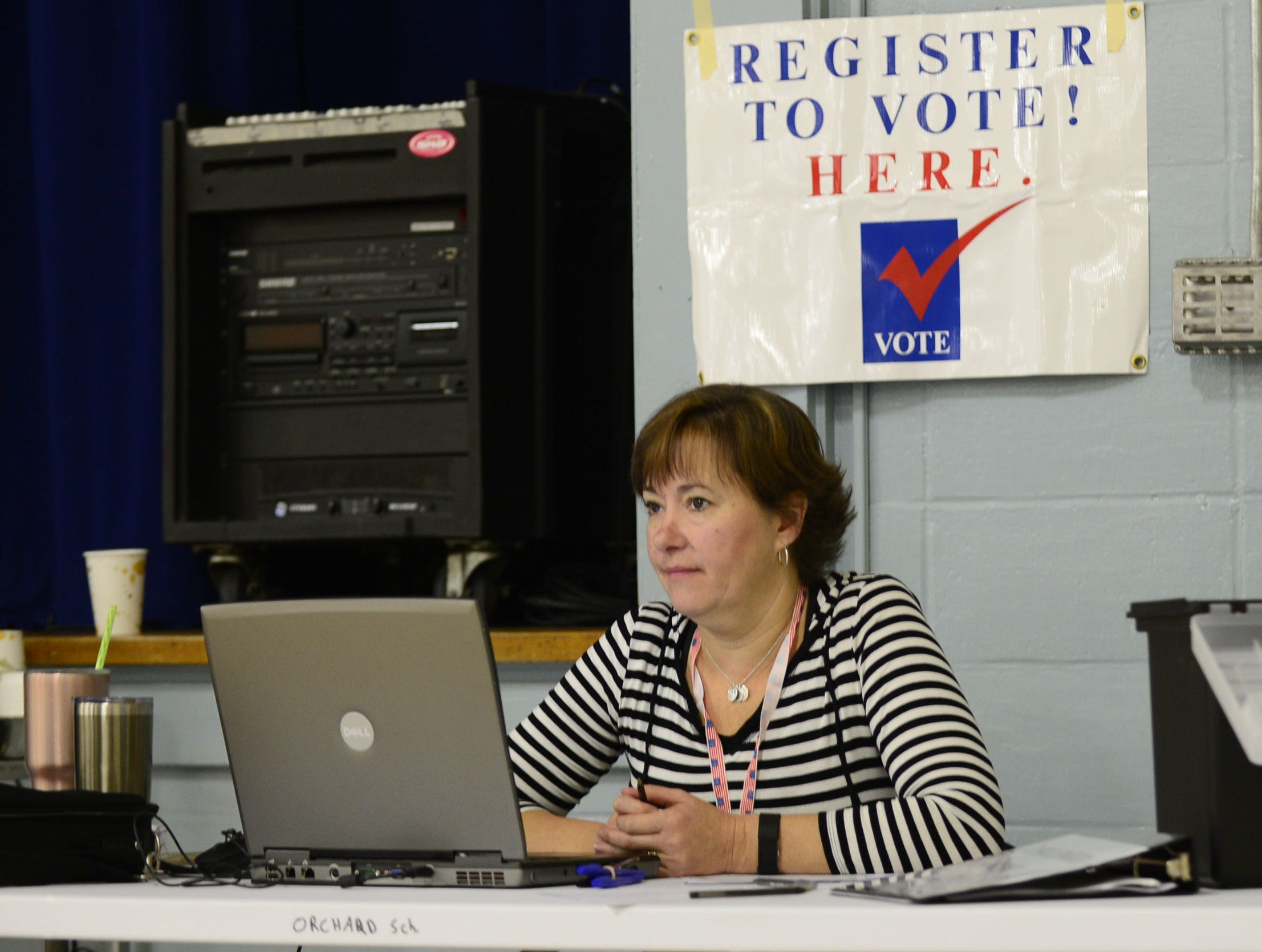 Andrea Leo, public service specialist for the city of South Burlington, waits for people who want to register to vote on election day, Nov. 6, 2018, at the Orchard School in South Burlington. Leo said she had signed up 8 people in the first 90 minutes of voting.