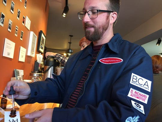 """Samuel Wisniewski, co-founder of Alice & the Magician, displays scent samples from the company at the Lucky Next Door cafe during the """"AutoBiography"""" event in Burlington on Sunday, Nov. 4, 2018."""