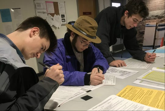 Same-day registration: University of Vermont students (left to right) David Sileo, Nick Mologne and Simon Carruthers complete paperwork a the polls prior to voting at Fletcher Free Library in Burlington on Tuesday, Nov. 6, 2018.