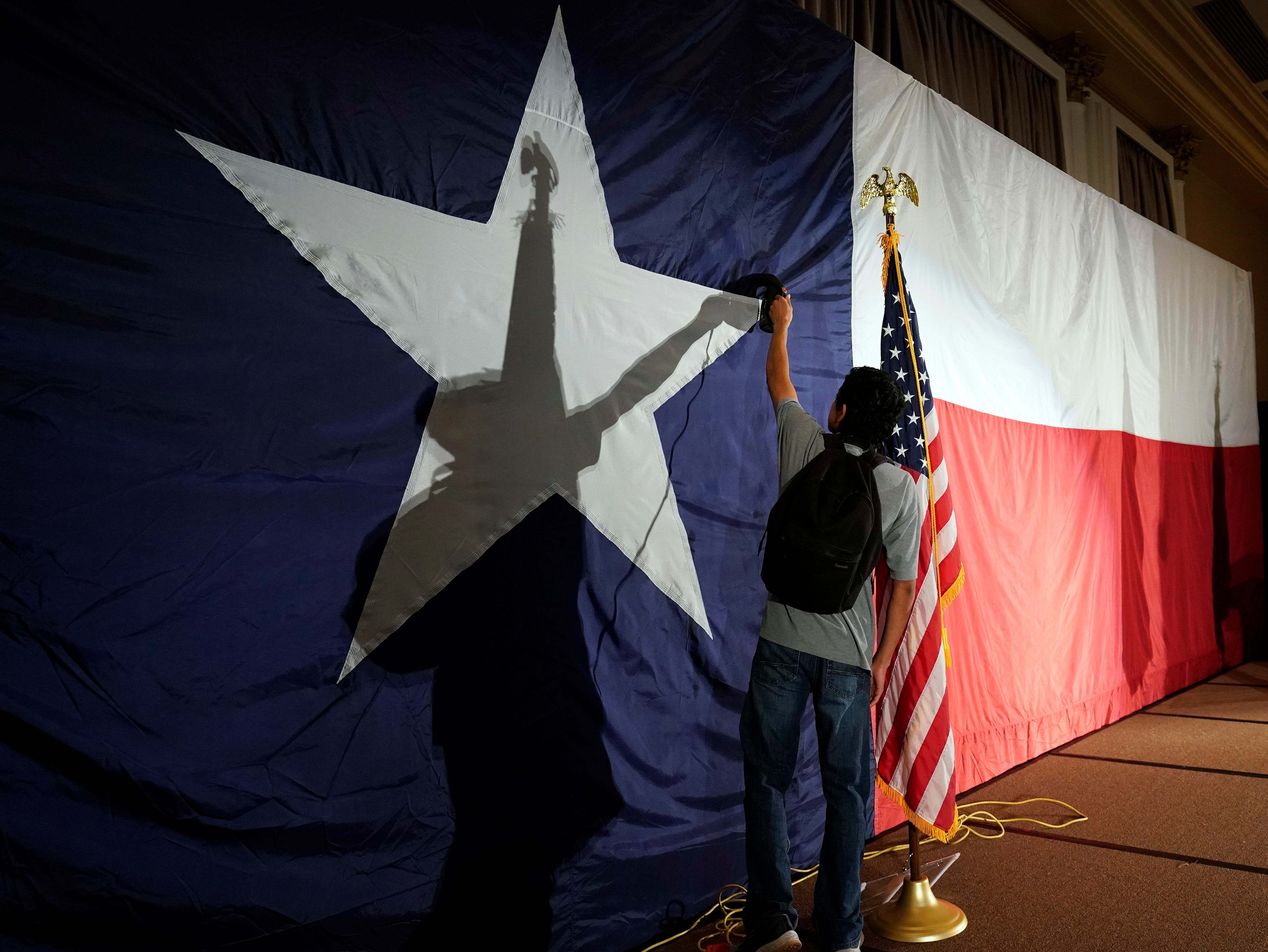 Jose Maybit Lopez, an intern for Sen. Ted Cruz, R-Texas, campaign, uses a steam iron on a Texas flag before an election night party, Tuesday, Nov. 6, 2018, in Houston. (AP Photo/David J. Phillip)