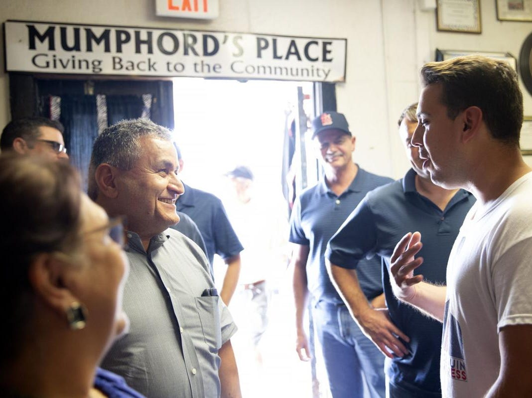 Democratic candidate Eric Holguin visits with a man that identified himself only as Mike and other prospective voters while they wait in line to order at Mumphord's Place Bar-B-Q Tuesday. Holguin is challenging incumbent Michael Cloud for the District 27 seat.