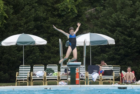 Emma Reynolds jumps in the pool at the Kingston Estates Swimm Club in Cherry Hill in a June 2011 file photo.