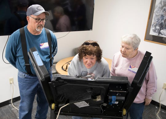 Joyce Thomas, middle, receives help from Jeff See and Dorothy Morehouse as she votes Tuesday morning due to the fact she is visually impaired. Voters with visual impairments get help from a Republican and a Democratic poll workers.