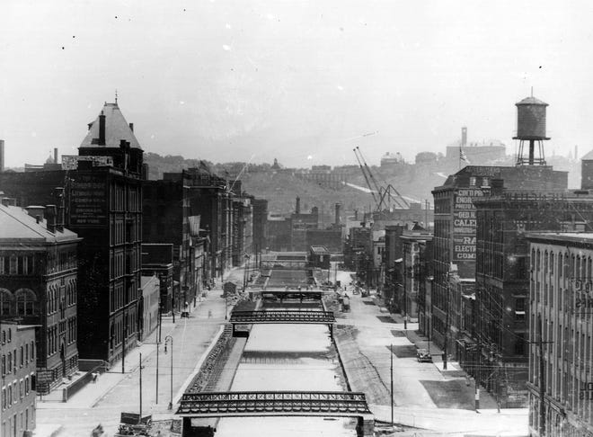 UNDATED: The Erie Canal in Cincinnati, Ohio flanked by Canal Streets (now Central Parkway), looking east with Mount Adams in the distance. Rashig School, three story building is pictured near left.