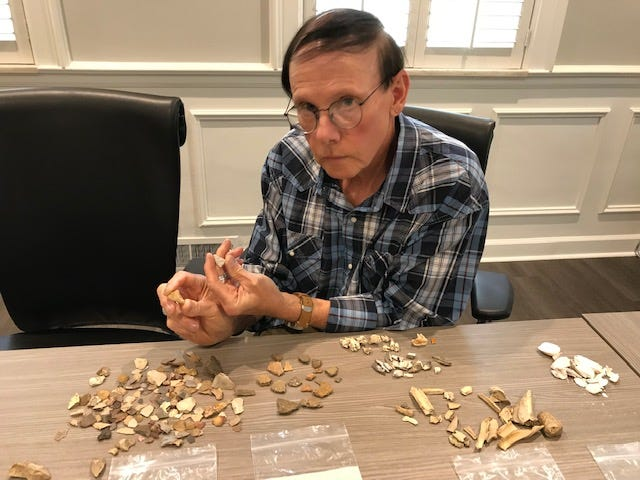 University of Cincinnati archaeologist Ken Tankersley with artifacts he and his students found in a surface search of a hillside by the Cincinnati Waldorf School in Mariemont. He's pictured here Oct. 30, 2018, holding an arrowhead and a human bone fragment.