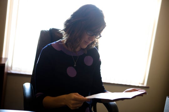 Meg Wittman, Right to Life of Greater Cincinnati executive director, looks at a letter from her grandmother while in her office the Right to Life of Greater Cincinnati office in Cincinnati on Oct. 23, 2018.