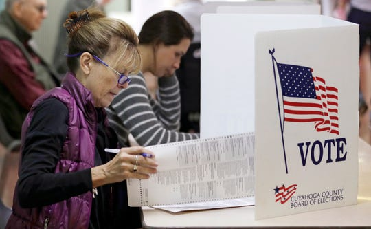 Patricia Wagoner looks over the ballot while voting, Tuesday, Nov. 6, 2018, in Gates Mills, Ohio. Across the country, voters headed to the polls Tuesday in one of the most high-profile midterm elections in years. (AP Photo/Tony Dejak)