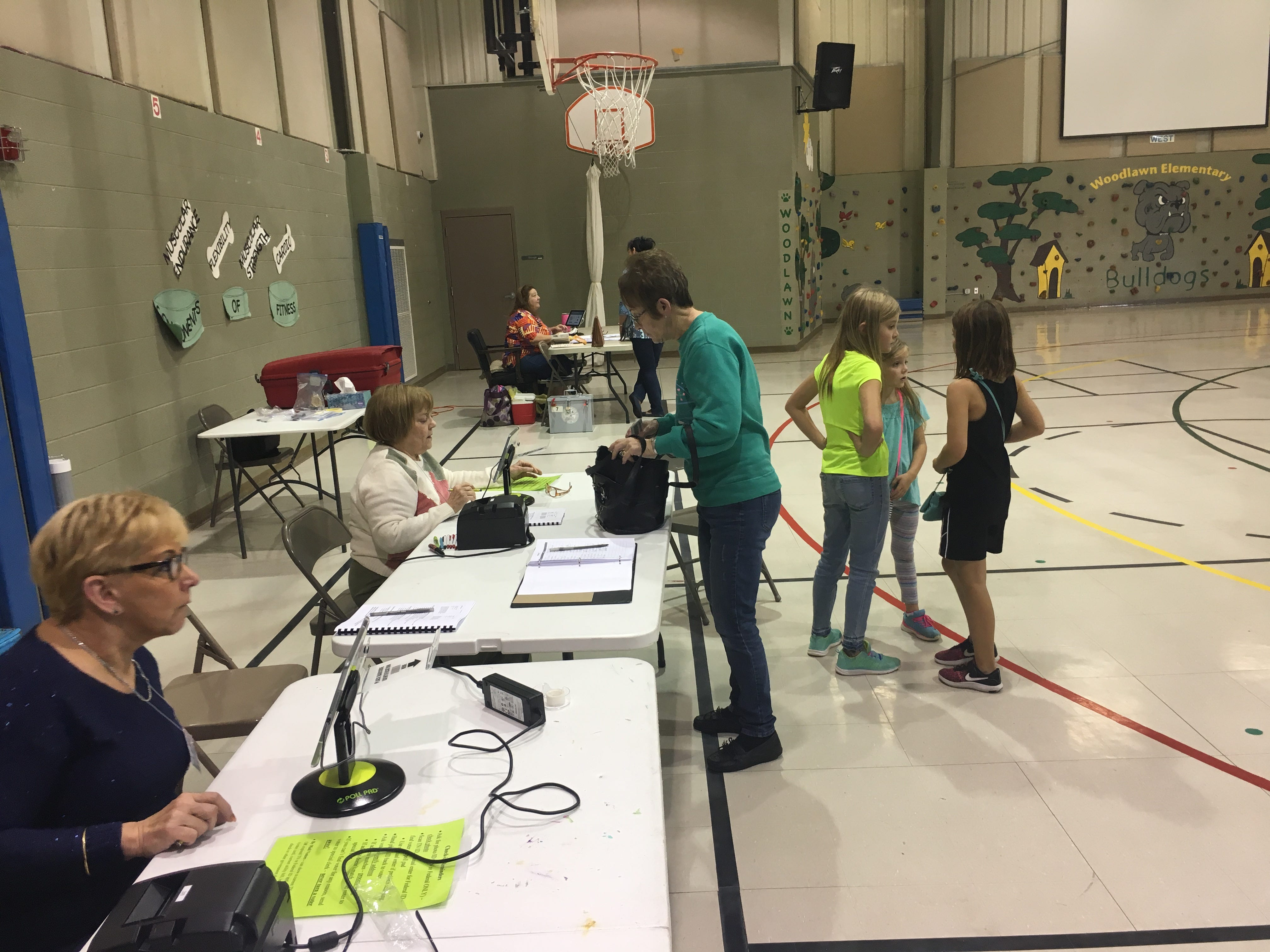Kids chat while parents sign in to vote at Woodlawn Elementary on Tuesday, Nov. 6, 2018.