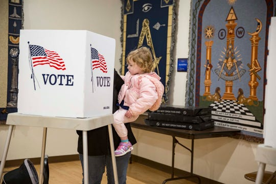 Heather Sharp with her daughters Cassandra, right, and Arianna, bottom left, casts her ballot in the midterm elections at the Masonic Temple, Tuesday, Nov. 6, 2018, in Indianola, Iowa.