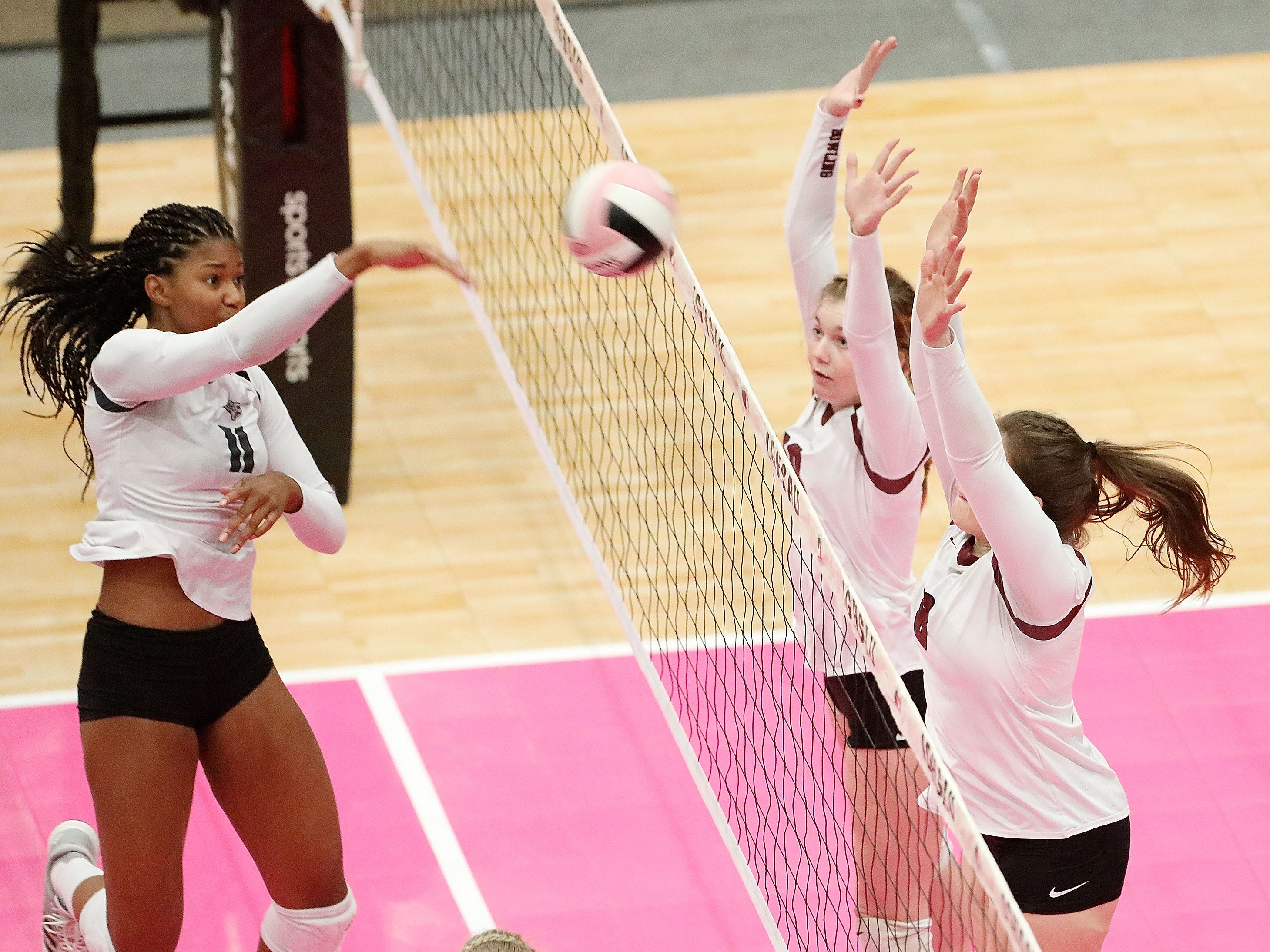Ankeny Centennial's Devyn Robinson (11) hits the ball over the net as Dowling Catholic's Piper Kirchhoff (10) and Jacey Koethe (8) try to block during the quarterfinals of the 2018 Girls' High School State Volleyball Tournament at the US Cellular Center in Cedar Rapids on Tuesday, November 6, 2018. (Cliff Jette/The Gazette)