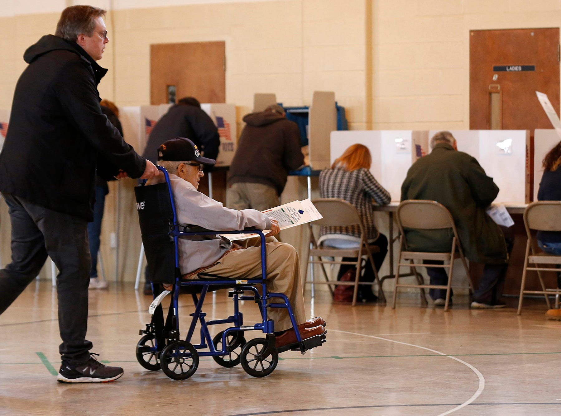 Joe Giacalone, of Commerce Township, helps his father and Army veteran Ignatius Giacalone, 97, also of Commerce Township, to vote at Union Lake Baptist in Commerce Township on November 6, 2018. Giacalone fought in World War II serving two tours in Europe and said he felt proud to be able to vote again.