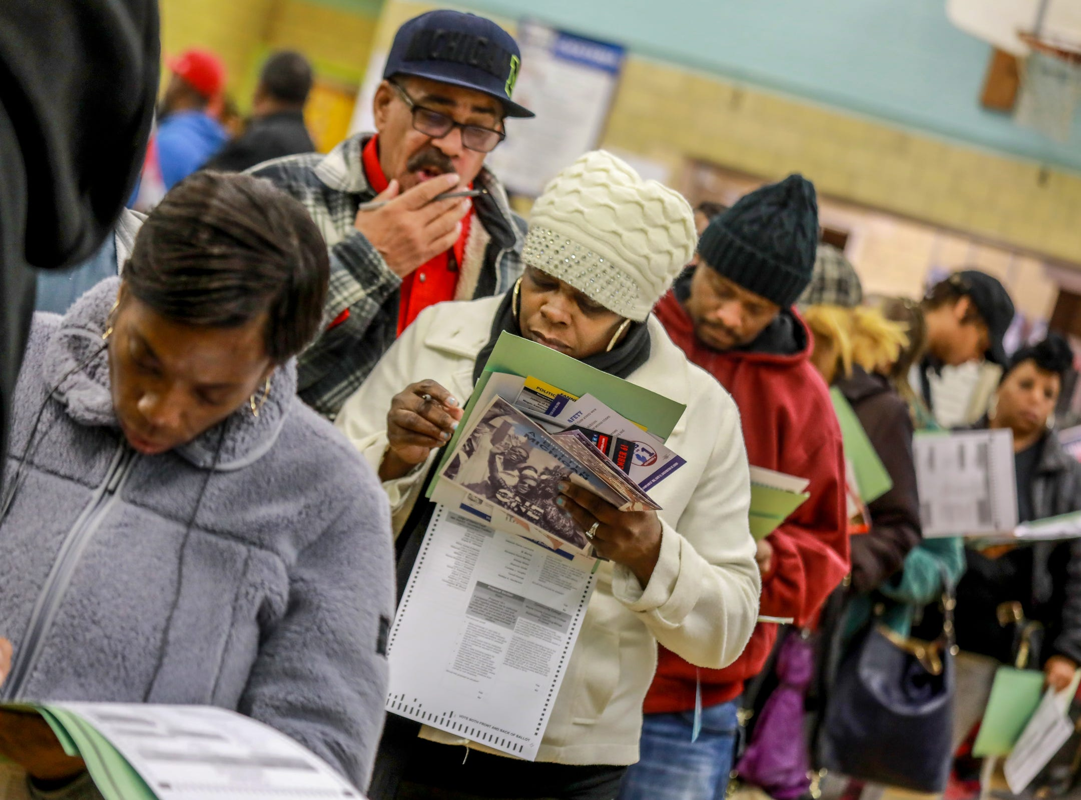 Lela Jamison, 53, of Detroit looks over her ballot as she stands in line waiting to vote at Bow Elementary School  where multiple precincts are located for the midterm elections in Detroit on Tuesday, Nov. 6, 2018.