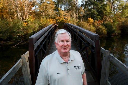Kent Hall, associate director for Honor For All, stands Oct. 25 on the bridge that follows a trail in Memorial Park in Williamston that will be renamed to honor veterans and first responders lost to suicide due to post-traumatic stress and traumatic brain injury. Hall, who suffers from post-traumatic stress disorder, is a convicted serial bank robber and now a city council member.