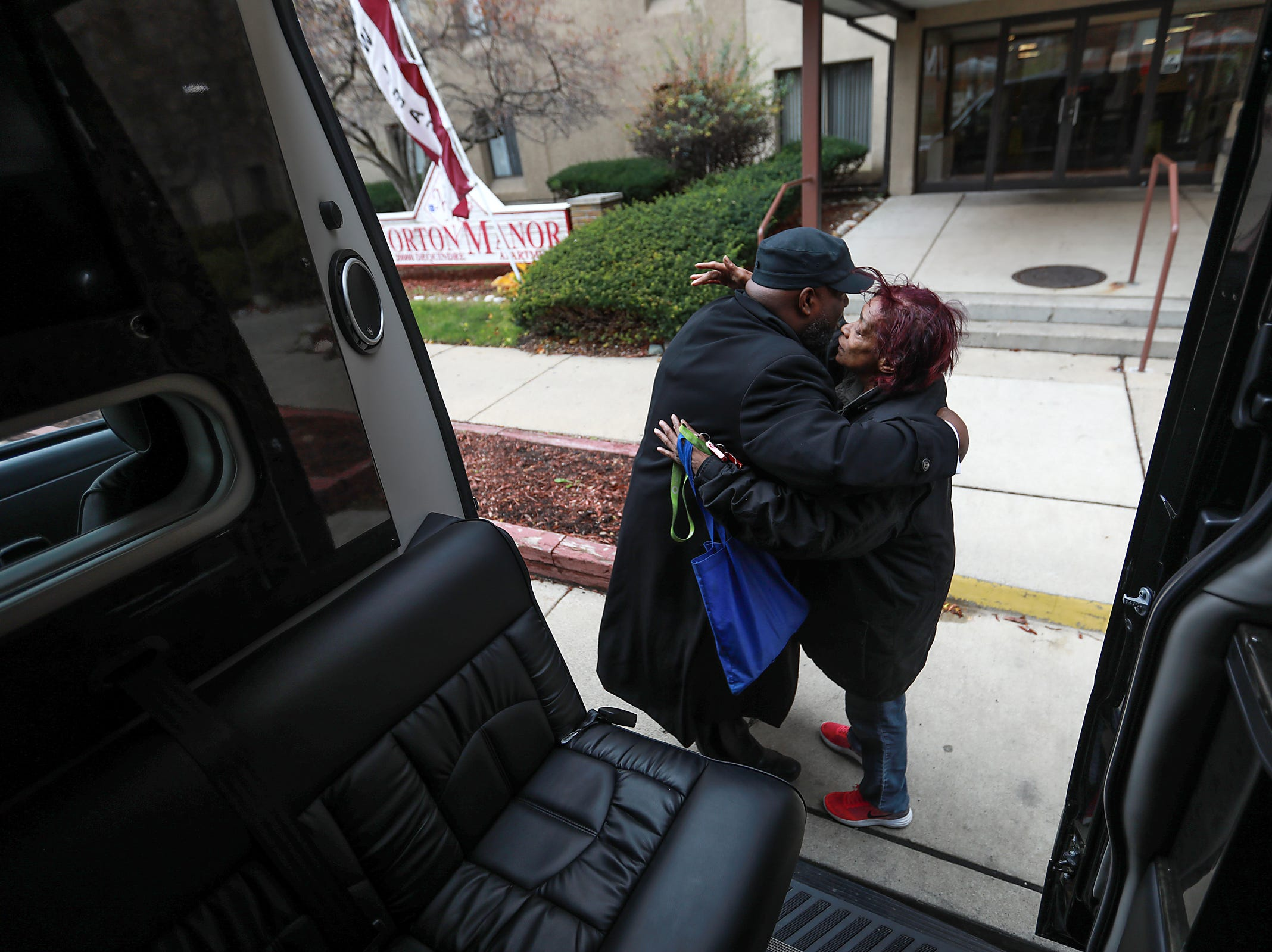 Calista Sanders, 73, of Detroit gives Pastor Terrell Jackson, 42, of Eastpointe, a hug she received a ride to the polls in a Mercedes limo bus, organized by Clora Funeral Home, for the midterm elections in Detroit on Tuesday, Nov. 6, 2018. Sanders said she always votes unless she can't get a ride to the polls.