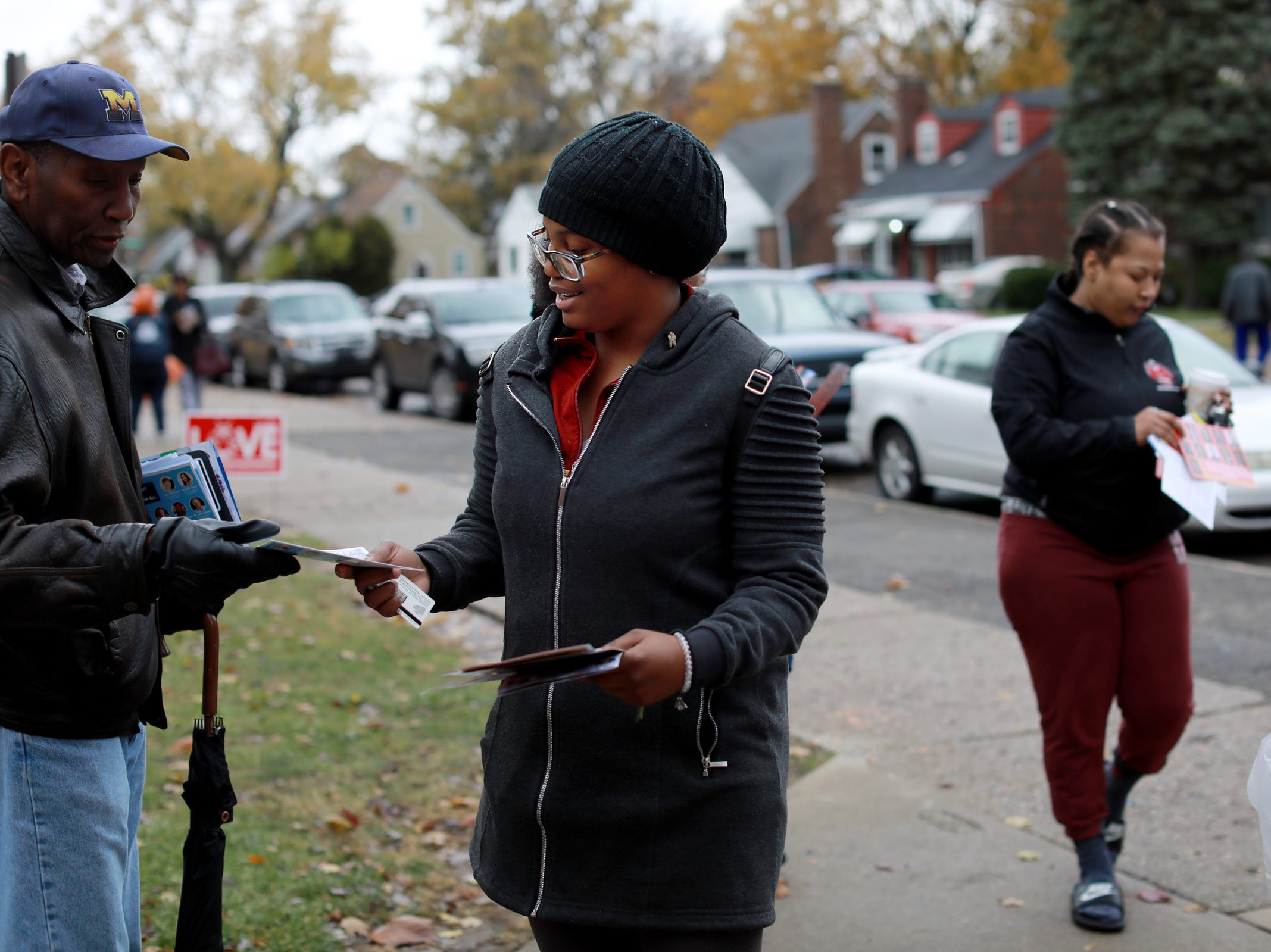 Kieara Morgan, 22, of Detroit receives political flyers as she walks into Bow Elementary to vote in midterm elections in Detroit on Tuesday, Nov. 6, 2018.