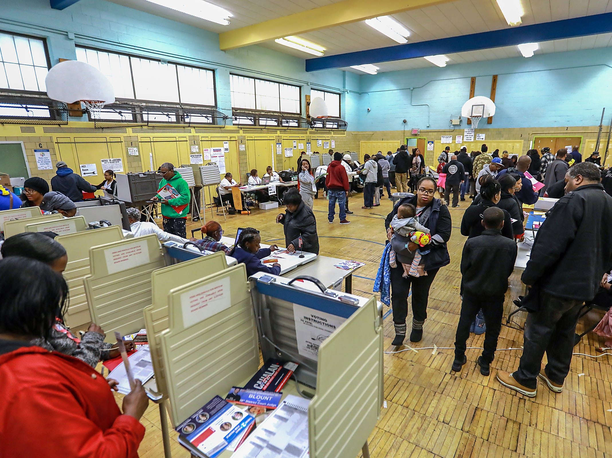 Voters stand in line waiting to vote at Bow Elementary School where multiple precincts are located for the midterm elections in Detroit on Tuesday, Nov. 6, 2018.