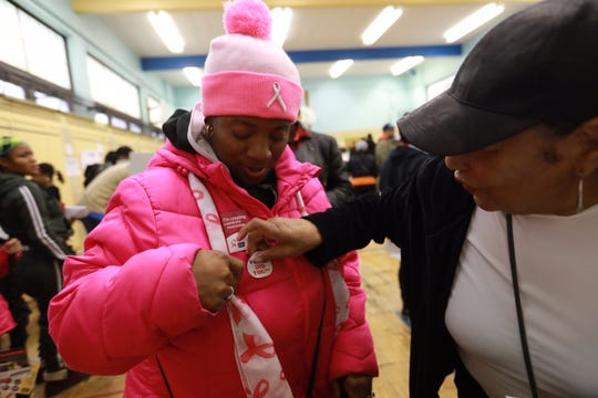 Bernadette Sadler, 53, Detroit, receives a voted sticker from election poll official Betty Hammond, 79, Detroit, at Bow Elementary-Middle School in Detroit on Tuesday, November 6, 2018.