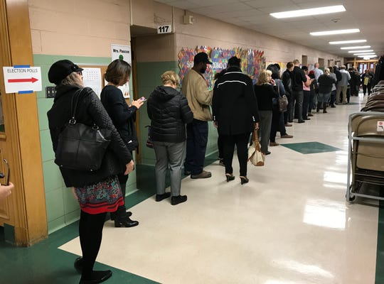 A line of voters wait in the hallway outside the gymnasium at Monteith Elementary School to cast their ballots in the midterm election on Tuesday, Nov. 6, 2018 in Grosse Pointe Woods.