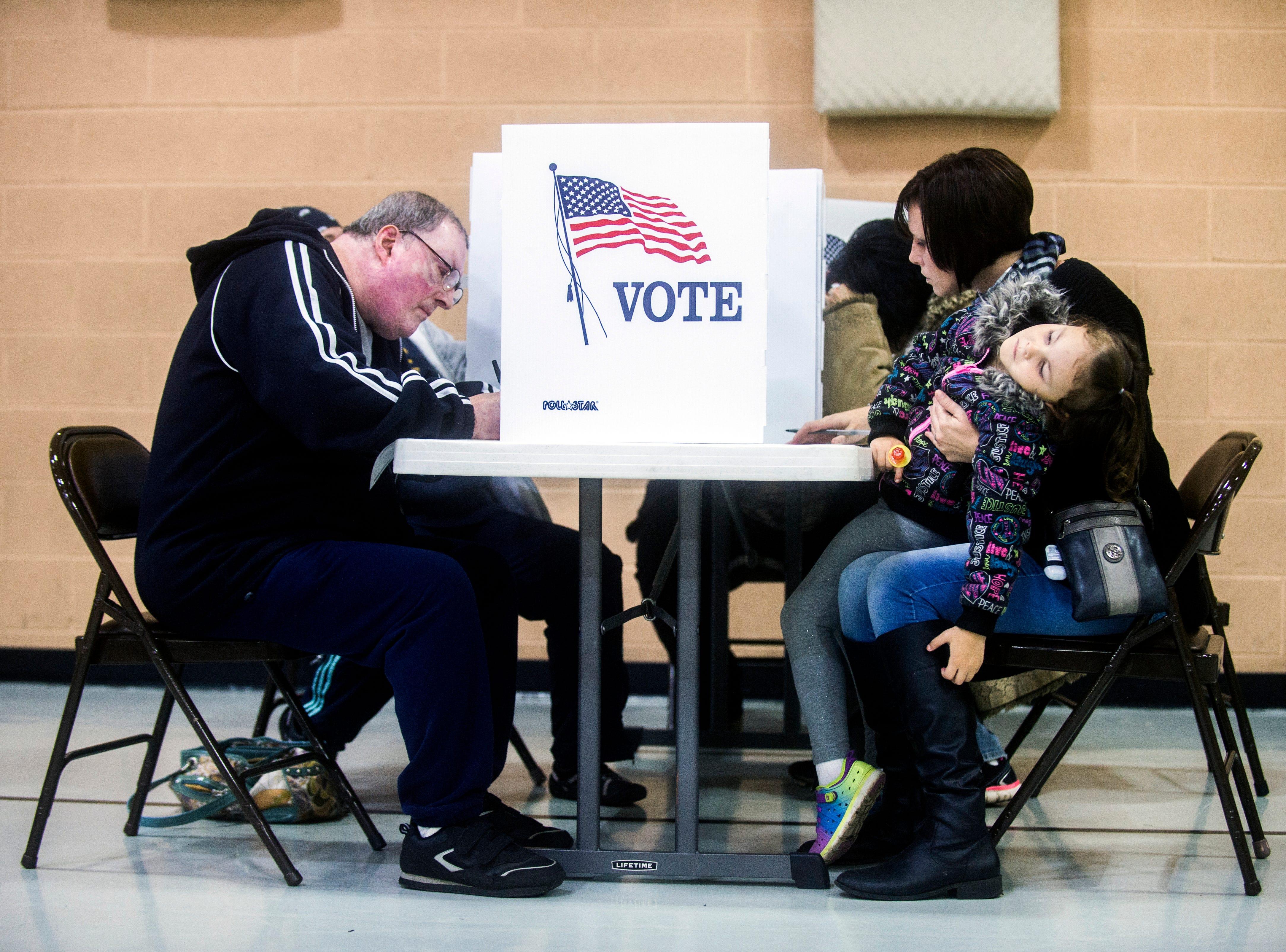 Cora Maynard, 4, grows tired as her mother, Davison resident Rachel Maynard, takes her time voting on Tuesday, Nov. 6, 2018 at First Baptist Church of Davison, Michigan.