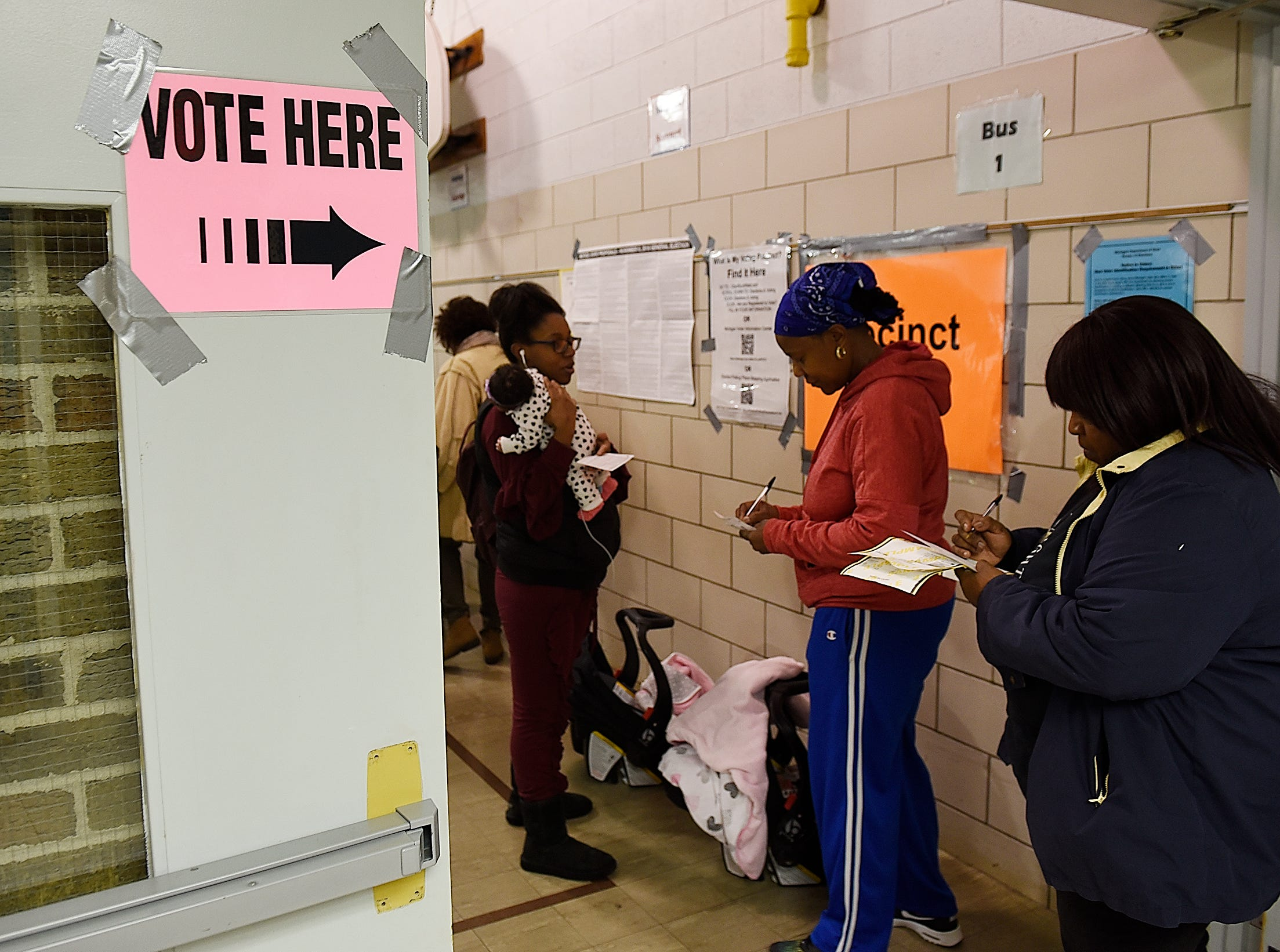 Vivien Mckenzie, 54, center, of Southfield and Sharon Carr, 62, of Southfield fill out applications to vote.