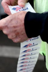 Doug Leaf, a ballot box security guard, gives stickers to voters at the drive-up drop box in Salem, Ore., on Election Day, Tuesday, Nov. 6, 2018.