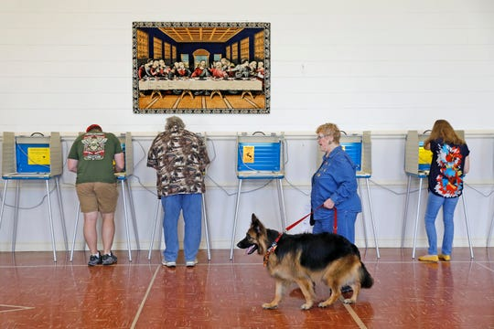 Susie Nelson, second from right, votes with German shepherd Cali at Trinity United Methodist Church in Poquoson, Va., Tuesday, Nov. 6, 2018.