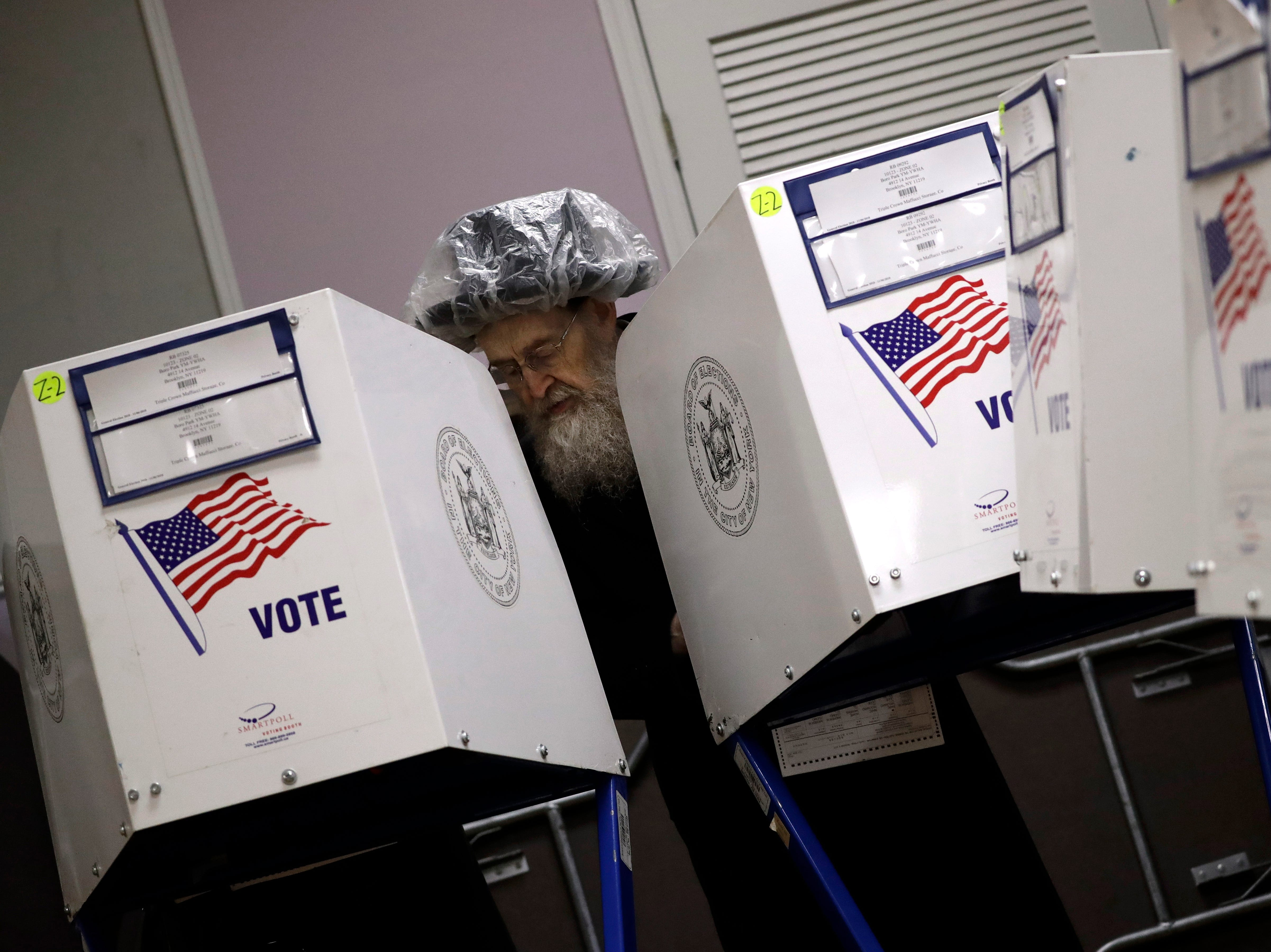 An orthodox Jewish man fills out his ballot papers at a polling center on Tuesday, Nov. 6, 2018, in Brooklyn borough of New York.
