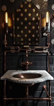 AT HOME for release OCTOBER 2018 HOME TOUCH Caption 5: The patina of the copper pipes influenced the choice of the Victorian-style wallpaper in this surprise steampunk powder room in San Francisco. Andre Rothblatt designed the sconces on either side of a simple, antique-style mirror to highlight a cohesive space.