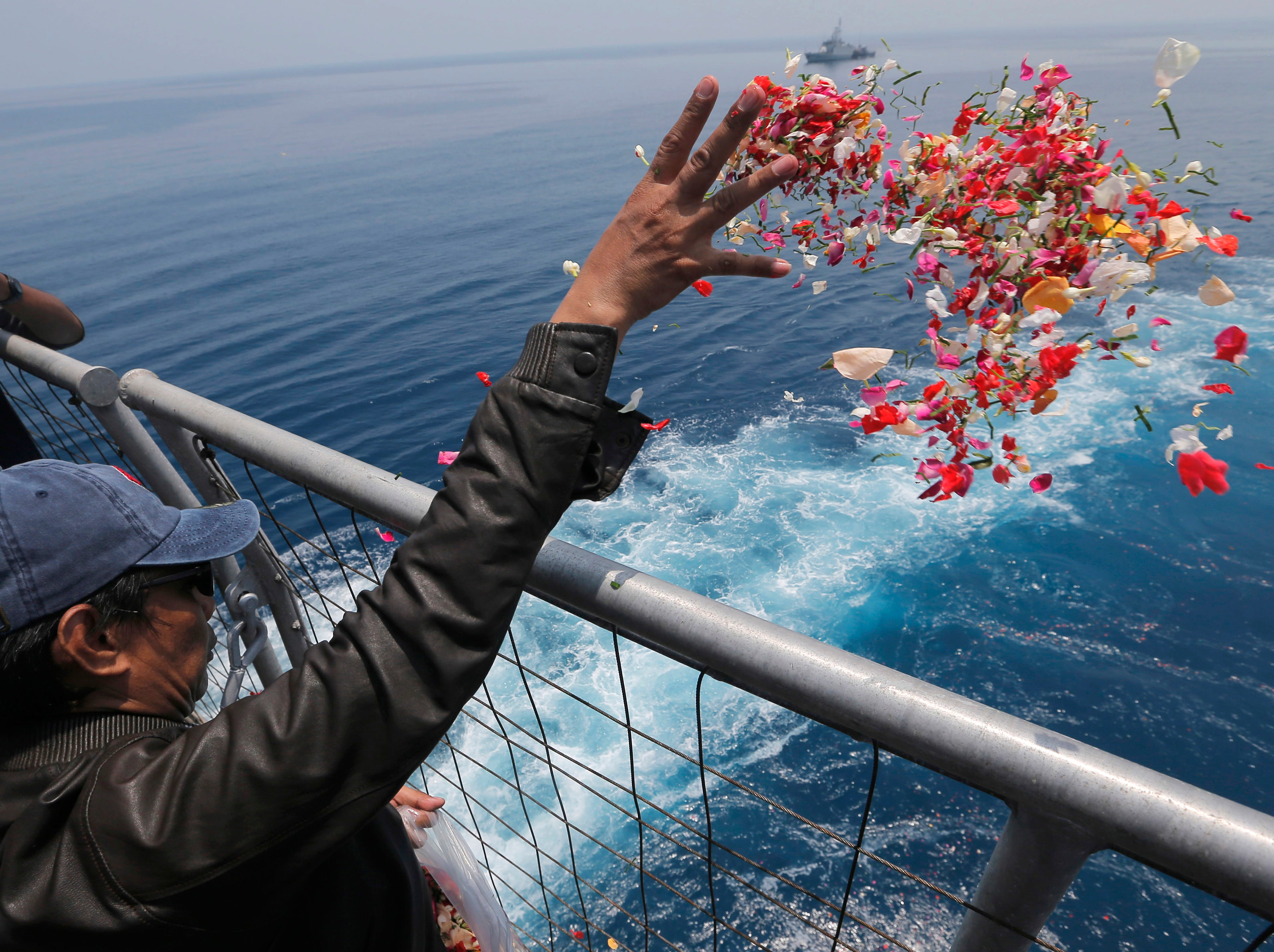 A relative sprinkles flowers for the victims of the crashed Lion Air flight 610 from an Indonesia Navy ship in the waters where the airplane is believed to have crashed in Tanjung Karawang, Indonesia, Tuesday, Nov. 6, 2018.