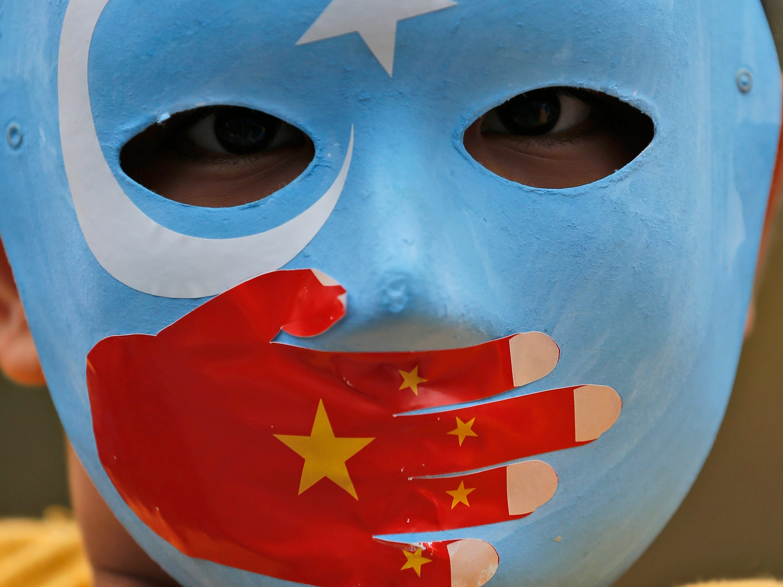 "A child from the Uighur community in Turkey wears a mask in the colors of the ""East Turkestan"" flag, with a painted hand with the colours of China's flag, during a protest in Istanbul, Tuesday, Nov. 6, 2018. Muslim Uighurs in the far-western Xinjiang province allege oppression by the Chinese government."