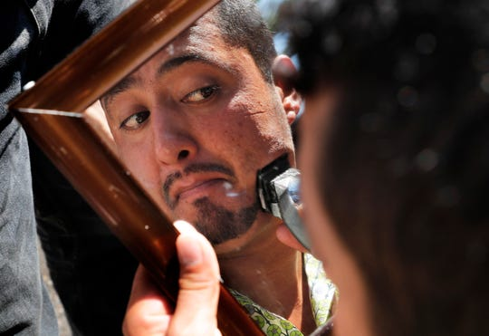 A Central American migrant trims his facial hair in a shelter at the Jesus Martinez stadium in Mexico City, Tuesday, Nov. 6, 2018.
