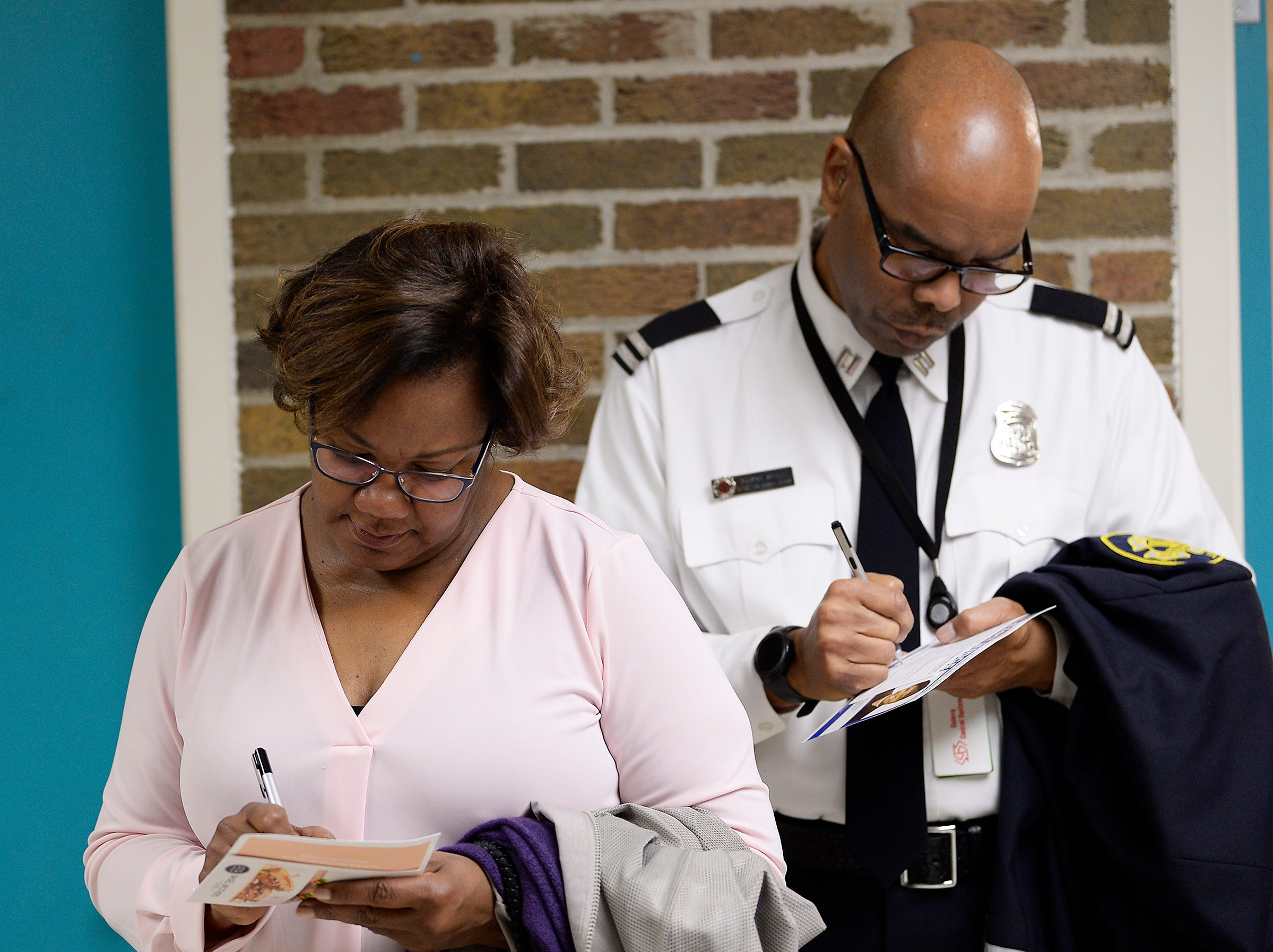 Kelly Small and husband Dwayne Small of Southfield fill out voting cards while waiting in line at Adler Elementary School in Southfield.