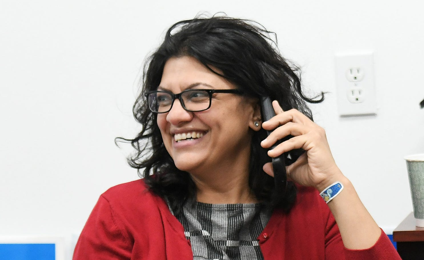 Rashida Tlaib, left, Democratic candidate for Congress in Michigan's 13th District, makes phone calls at the Democratic field office in Detroit on Monday.