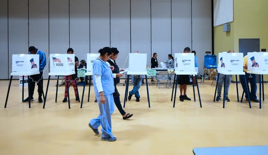 People vote from booths inside the gymnasium at the Barack Obama Prep Academy on November 6, 2018 in Los Angeles, California.