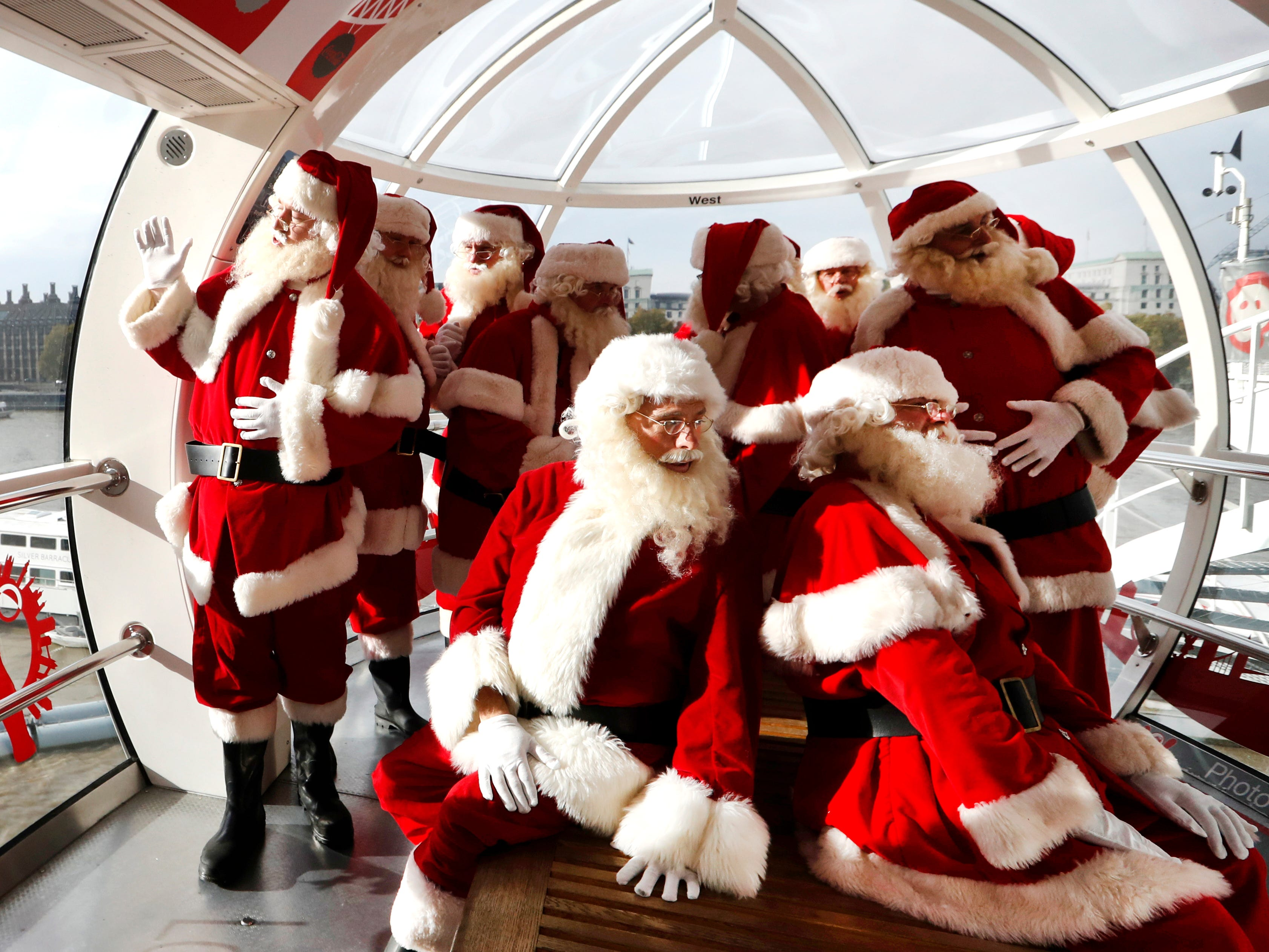 Santas from the Santa School take a look at the London skyline from a pod in the London Eye, Tuesday, Nov. 6, 2018. These Santas will be working in shops and malls around London as the Christmas season approaches.