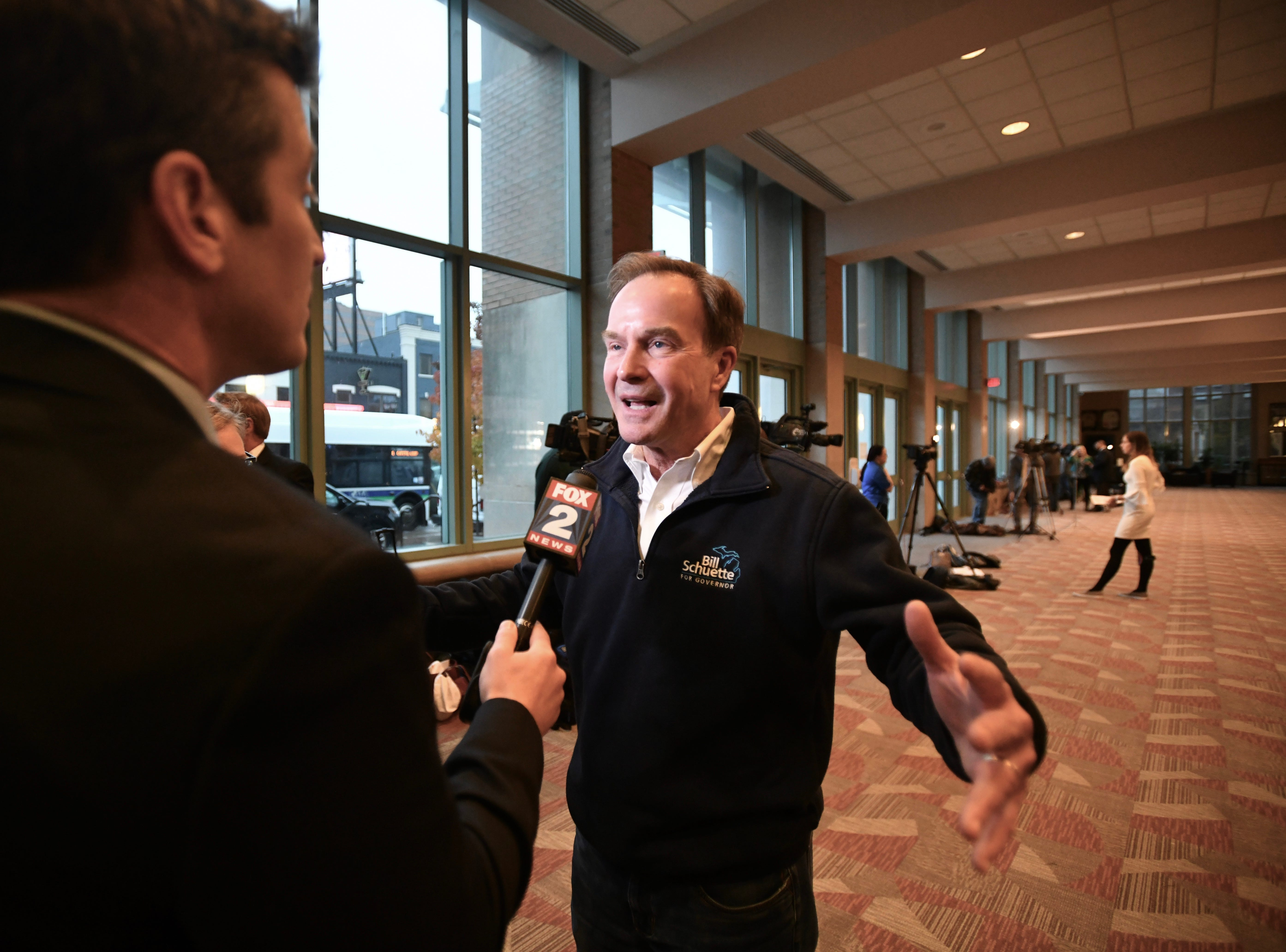 Bill Schuette talks with a TV reporter at the Lansing Center on Tuesday evening before the GOP election night party on November, 6, 2018.