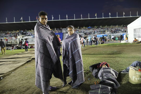 Central American migrant Jerson Suazo, left, stands with his wife Anabel Pineda next to their six-year-old son Fernando, at a shelter in the Jesus Martinez stadium, in Mexico City, Monday, Nov. 5, 2018.