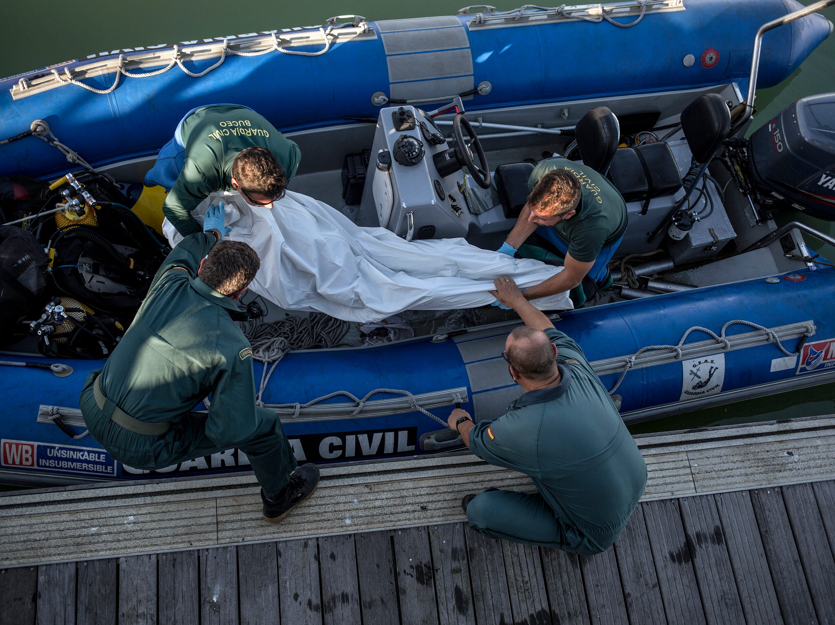 Members of the Spanish civil guard unload the remains of a migrant that was recovered off the coast off Barbate, Spain, Tuesday, Nov. 6 2018. Spain's maritime rescue service says at least 17 people have died trying to reach Spanish territory in boats departing from North Africa.