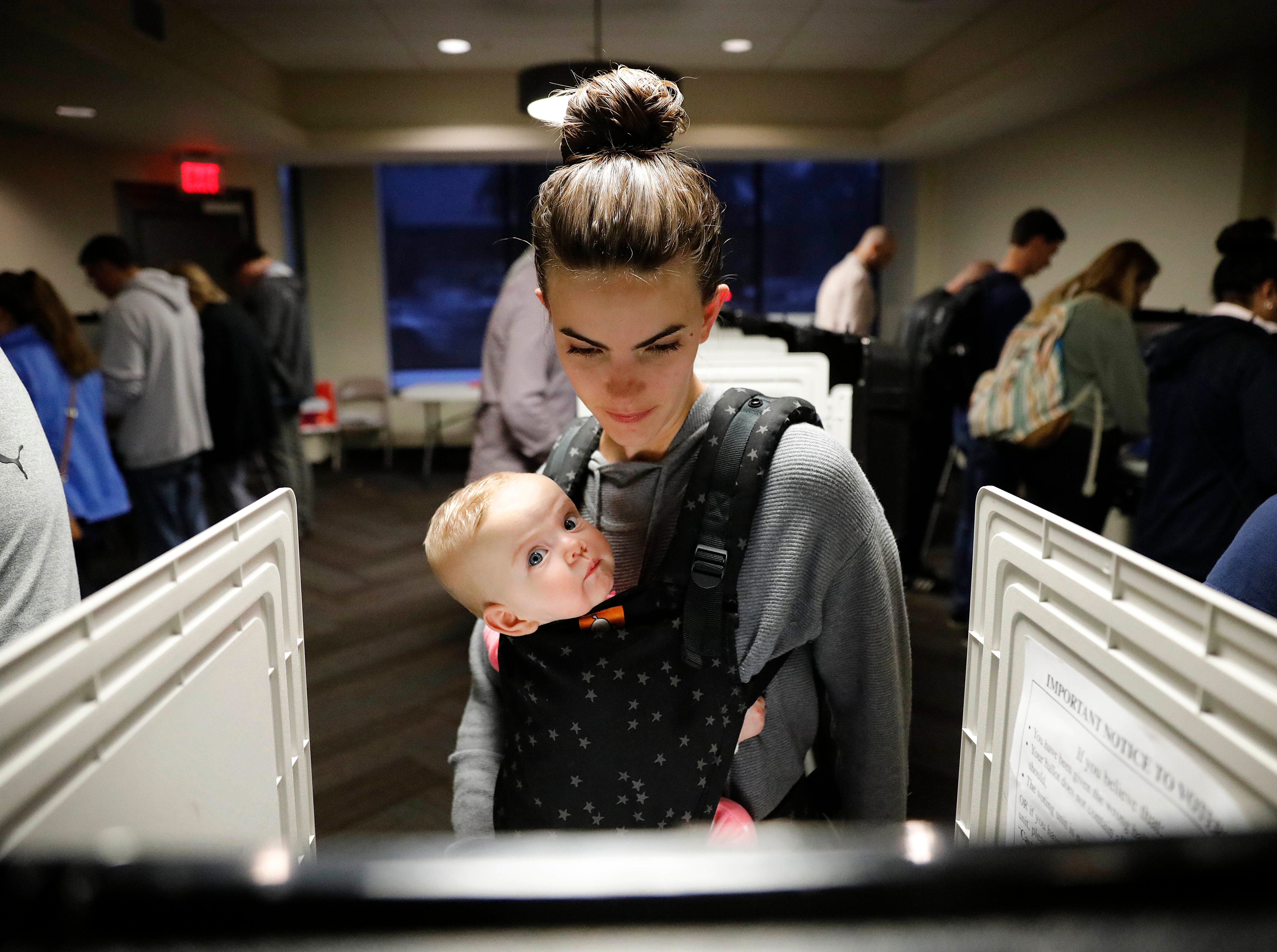 Kristen Leach votes with her 6-month-old daughter, Nora, on election day in Atlanta, Tuesday, Nov. 6, 2018.