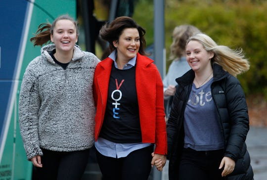 Michigan Democratic gubernatorial candidate Gretchen Whitmer, center, walks from her campaign bus to the polling place with daughters Sherry, left, and Sydney, Tuesday at St. Paul Lutheran Church in East Lansing.