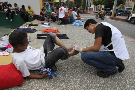 Honduran migrants are taken care of by Guatemalan Red Cross volunteers, in Tecun Uman, Guatemala, Thursday, Oct. 18, 2018.