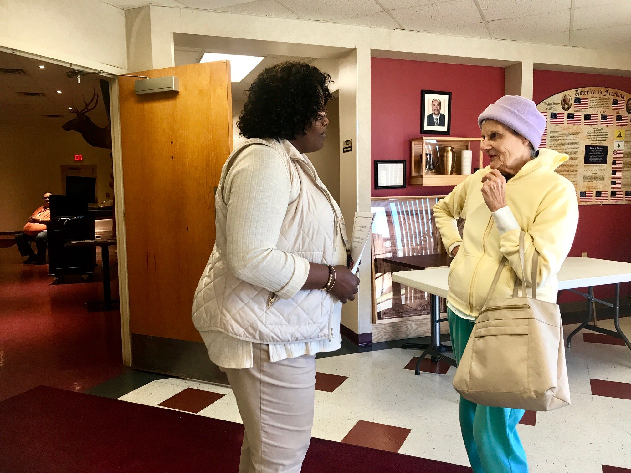"Poll worker Roxanne Brown, left, talks with a voter at Elmira Elks Lodge 62. Brown reported the first person voted at 6:01 a.m. and voting has been ""busy, then slow, then busy again."""