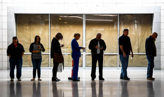 Voters wait in line to cast their ballot at the Washington Square Mall voting center Tuesday morning, November 6, 2018.