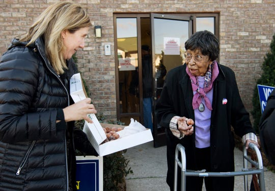 "Democratic candidate for state representative, Edie Hardcastle, left, offers Donut Bank donut holes to 95-year-old Mamie Dulin after she voted at Memorial Baptist Church Tuesday morning. ""She wanted to vote today,"" volunteer driver Deborah Wagner said of Dulin. ""We were like, 'She's gonna get here, 'cause this is what she wanted to do.'"" The voting center had a continuous trickle of voters for the first five hours since the polls opened at 6 a.m. according to workers. """