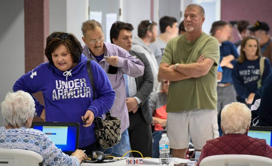 Suzanne Kasinger, Evansville, signs in at the St. James West voting center. Voters formed a line extending out the door and down the sidewalk Tuesday around noon, November 6, 2018.